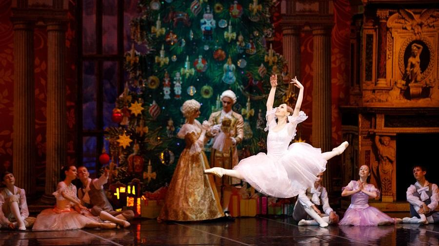 ballet dancer leaping in front of a large Christmas tree