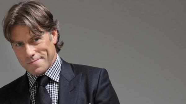 John Bishop smiling, wearing a suit and tie.