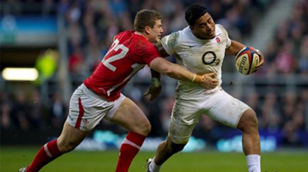 Image of an England and Welsh rugby player reaching for the ball