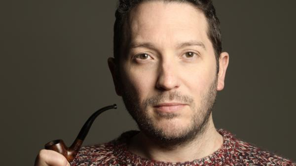 image of jon richardson holding a pipe