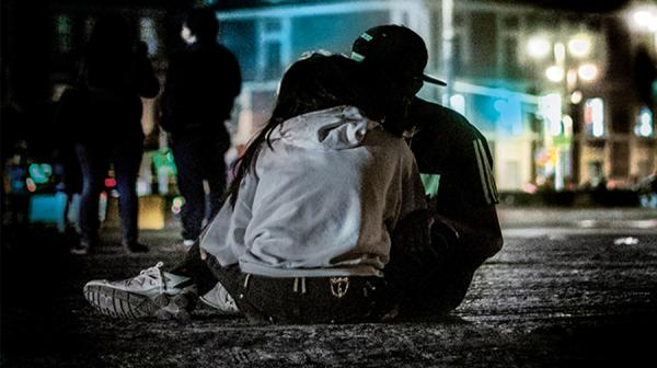 A photo from the back of a young man and woman embracing, in an urban environment